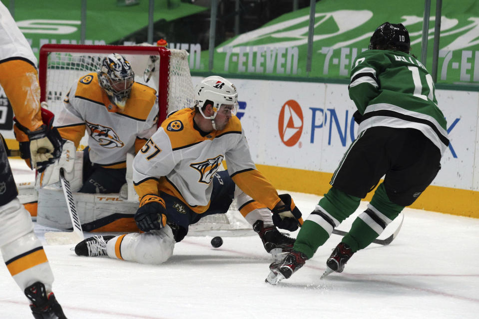 Nashville Predators goaltender Pekka Rinne (35) and defenseman Dante Fabbro (57) defend against a shot by Dallas Stars center Ty Dellandrea (10) in the second period during an NHL hockey game on Sunday, March 7, 2021, in Dallas. (AP Photo/Richard W. Rodriguez)