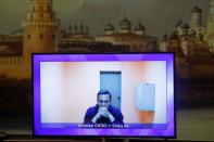 Russian opposition leader Alexei Navalny is seen on a screen via a video link during a court hearing to consider an appeal on his arrest, outside Moscow