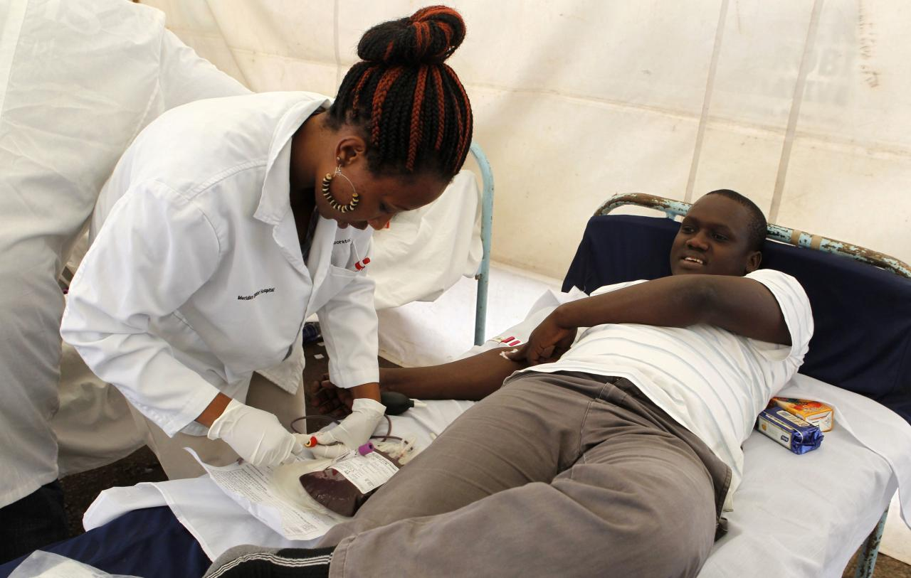 A man donates blood at a temporary donation centre for the injured victims of a crossfire between armed men and the police at the Westgate shopping mall, in Kenya's capital Nairobi September 22, 2013. Islamist militants were holed up with hostages on Sunday at a shopping mall in Nairobi, where at least 59 people have been killed in an attack by the al Shabaab group that opposes Kenya's participation in a peacekeeping mission in neighboring Somalia. REUTERS/Thomas Mukoya (KENYA - Tags: CIVIL UNREST CRIME LAW)