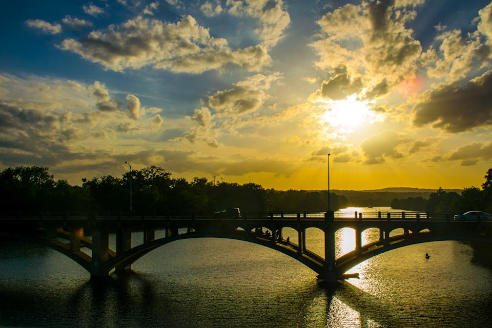 Crowds gather around the water to watch the bats on the XX bridge at sunset. (Getty Images)