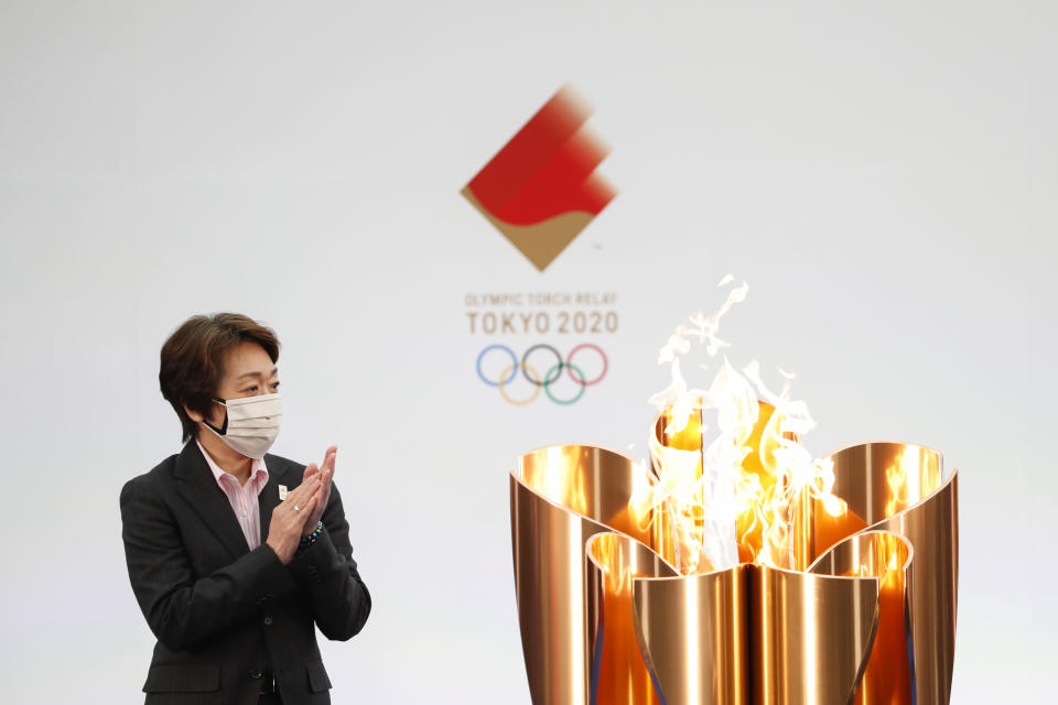 Tokyo 2020 Organizing Committee President Seiko Hashimoto applauds next to the celebration cauldron on the first day of the Tokyo 2020 Olympic torch relay in Naraha, Fukushima prefecture, northeastern Japan, Thursday, March 25, 2021. The torch relay for the postponed Tokyo Olympics began its 121-day journey across Japan on Thursday and is headed toward the opening ceremony in Tokyo on July 23. (Kim Kyung-Hoon/Pool Photo via AP)