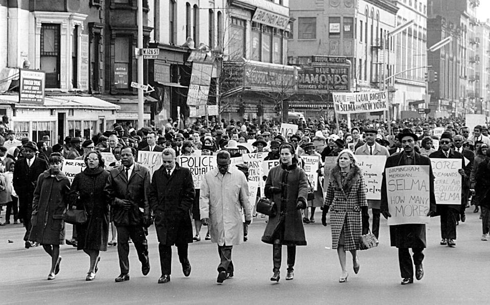 "Civil rights advocates march in Harlem to protest racial violence in Selma, Alabama. The ""Bloody Sunday"" police beatings of protesters there in March 1965 led to protests around the country; they also set the stage for the passing of the Voting Rights Act of 1965, which banned discriminatory voting practices and procedures, like literacy tests."