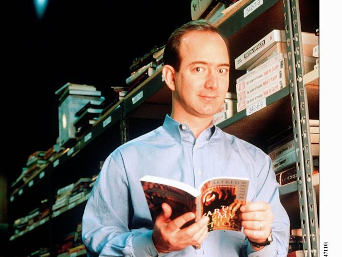 Jeff Bezos holds book and poses against book rack