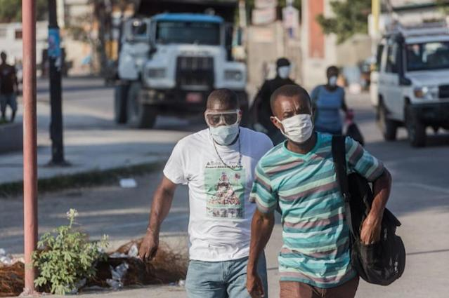 Two men wear masks as they walk in the streets of downtown Port-au-Prince on March 26, 2020. When the novel coronavirus first appeared in Haiti authorities and humanitarian experts panicked, worried about the country's decrepit health system -- but health officials say the virus may have already passed its peak (AFP Photo/Pierre Michel Jean)