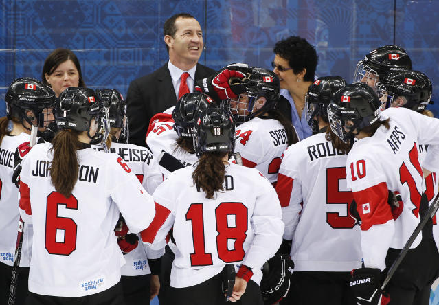 Canada head coach Kevin Dineen celebrates with players after Canada beat Switzerland 3-1 in a 2014 Winter Olympics women's semifinal ice hockey game at Shayba Arena, Monday, Feb. 17, 2014, in Sochi, Russia. (AP Photo/Julio Cortez)