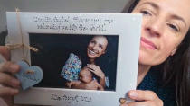 In this image taken from an online video interview with The Associated Press, Claudia Anghel, a Romanian midwife working in England, poses with a thank you card from a patient, in Nuneaton, England, Tuesday, July, 28, 2020. Anghel's success story as one of 600,000 Romanians in Britain is at the same time a telling sign of how the deficiencies of her home country's health care system and the bleak prospects for a better future for herself and her family have left huge gaps in Romanian society and its health care system. (AP Photo)