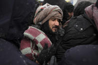 A migrant grimaces as he stands in a crowd waiting to be relocated during a snowfall at the Lipa camp northwestern Bosnia, near the border with Croatia, Saturday, Dec. 26, 2020. Hundreds of migrants are stranded in a burnt-out squalid camp in Bosnia as heavy snow fell in the country and temperatures dropped during a winter spell of bad weather after fire earlier this week destroyed much of the camp near the town of Bihac that already was harshly criticized by international officials and aid groups as inadequate for housing refugees and migrants.(AP Photo/Kemal Softic)