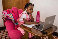 Lucie Ernest, 5, sits in front of a laptop as she follows her online class on February 18, 2021 in Port-au-Prince; she is luckier than many young Haitians