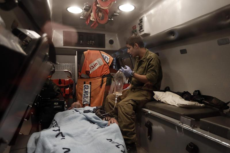 A wounded Israeli soldier is evacuated by ambulance on the Israel-Gaza border in southern Israel, Saturday, Nov. 10, 2012. An explosion targeted an Israeli military vehicle on the Jewish state's border with Gaza on Saturday and Israeli troops fired into the Palestinian territory killing several civilians and wounding at least 25, Gaza officials and witnesses said. (AP Photo / Tsafrir Abayov)