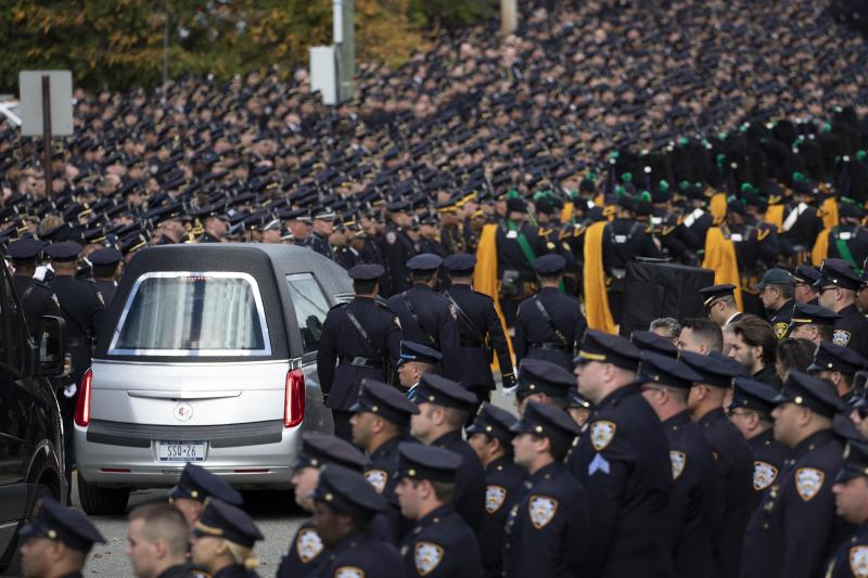 Thousands of police officers line a street in Monroe, N.Y. as the hearse bearing police officer Brian Mulkeen leaves the Church of the Sacred Heart, Friday, Oct. 4, 2019. Officer Mulkeen was fatally struck by two police bullets while struggling with an armed man after chasing and shooting at him Sunday in the Bronx borough of New York. It was the second time this year a New York City police officer has been killed by friendly fire. (AP Photo/Mark Lennihan)