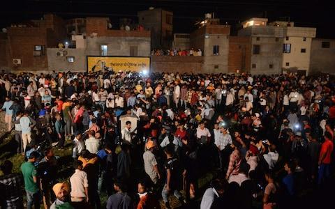 <span>Indian relatives and revellers gather around the bodies of the victims of a train accident during the Hindu festival of Dussehra in Amritsar </span> <span>Credit: NARINDER NANU/AFP </span>