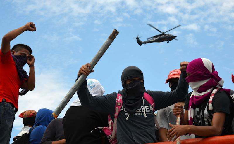 Young teachers block a major highway as they chant slogans, one holding a metal pipe, as a federal police helicopter flies overhead in Chilpancingo, Mexico, Thursday, April 11, 2013. The teachers, who are protesting an educational reform that will submit them to evaluation and loosen union control over hiring and firing, left peacefully after negotiating with police. (AP Photo/Alejandrino Gonzalez)