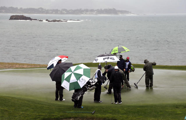 The playing group of Cameron Champ and Brice Garnett wait as greenskeepers work to remove standing water on the 18th green of the Pebble Beach Golf Links during the second round of the AT&T Pebble Beach Pro-Am golf tournament Friday, Feb. 8, 2019, in Pebble Beach, Calif. (AP Photo/Eric Risberg)