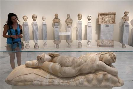 A tourist looks at a statue of a sleeping Maenad (AD 117-138) in the National Archaeological museum in Athens August 22, 2013. REUTERS/John Kolesidis