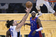 Orlando Magic center Nikola Vucevic (9) goes up for a shot in front of Detroit Pistons center Isaiah Stewart, obscured, and forward Jerami Grant (9) during the second half of an NBA basketball game, Tuesday, Feb. 23, 2021, in Orlando, Fla. (AP Photo/Phelan M. Ebenhack)