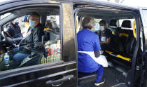Dr Tamara Joffe prepares to administer a Covid-19 jab using the AstraZeneca vaccine to Leslie Reid in the back of a London Taxi cab during the pilot project of pop up vaccination drive 'Vaxi Taxi' in Kilburn, London, Sunday, Feb. 28, 2021. The pilot scheme, funded by the Covid Crisis Rescue Foundation, aims to help ferry supplies and patients to temporary clinics set up in faith and community centres across the capital. People don't even need to leave the backseat if they didn't want to in order to receive their inoculation. (AP Photo/Alastair Grant)