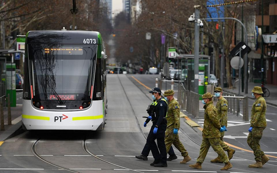 Victorian Police officers and ADF personnel are seen along Bourke street in Melbourne - JAMES ROSS/EPA-EFE/Shutterstock
