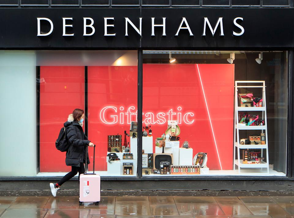 A woman walks past a Debenhams store in Manchester in the final week of a four week national lockdownPA