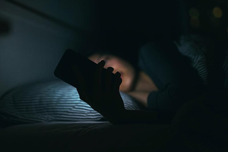 Young woman text messaging on smartphone while relaxing and lying on bed at night