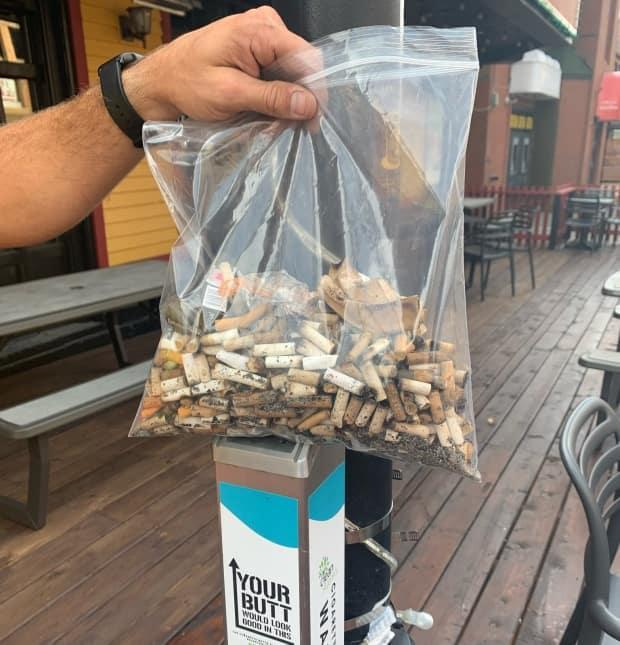 A bag of cigarette butts is collected from a receptacle as part of the Clean St. John's Butt Free YYT program. (Submitted by Karen Hickman - image credit)