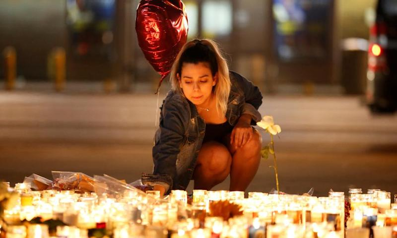 A woman lights candles at a vigil on the Las Vegas Strip. Fundraisers, food donations, and blood drives are taking place across the city.