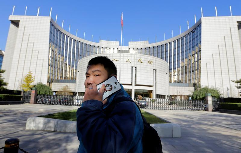 Man uses his mobile phone while walking past the headquarters of the PBOC in Beijing
