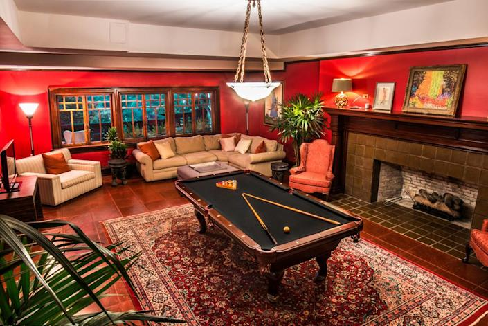 <p>Downstairs, the first level is mostly for entertaining. This is the traditionally colored billiard room with yet another Batchelder fireplace.</p>