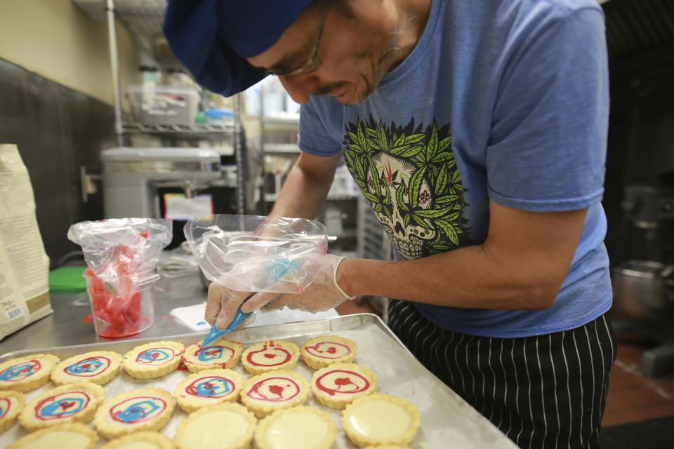 Baker Michael 'Miguel' Deluca decorates tarts at the Minerva medical dispensary on Tuesday, June 29, 2021, in Santa Fe, New Mexico. Cannabis was baked into the butter. (AP Photo/Cedar Attanasio)