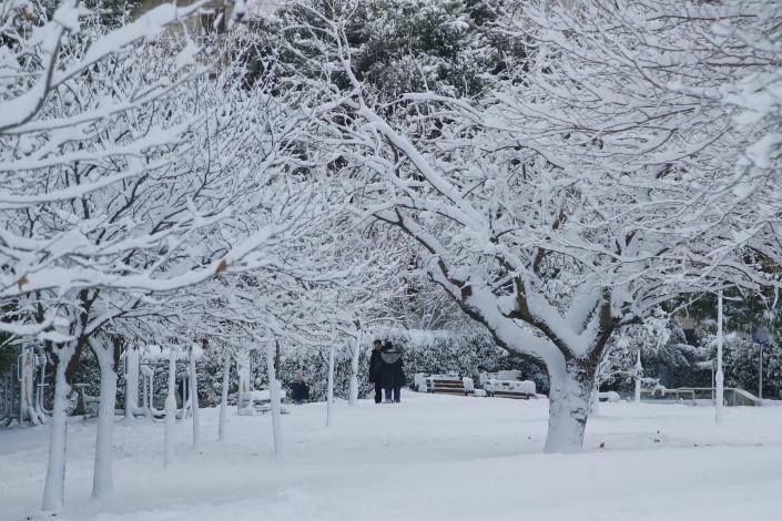 People enjoy the snow at a park in northern Athens, Tuesday, Jan. 8, 2019. Schools will remain closed across many parts of the country as a new cold weather front brings freezing temperatures and heavy snowfall. (AP Photo/Thanassis Stavrakis)