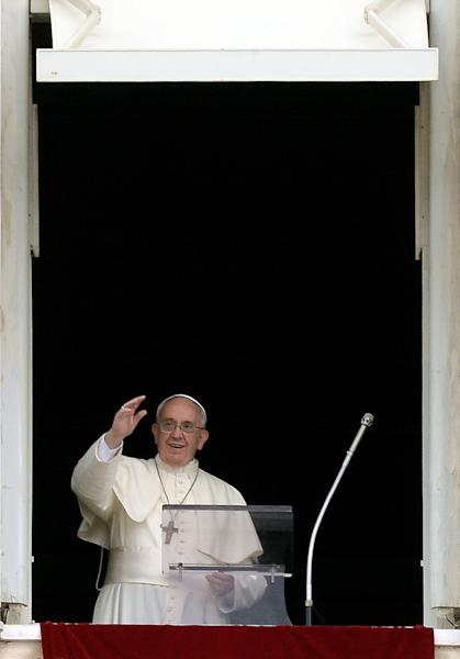 Pope Francis waves from the window of his study overlooking St. Peter's Square at the Vatican before leading his Sunday Angelus prayer on July 13, 2014 (AFP Photo/Filippo Monteforte)