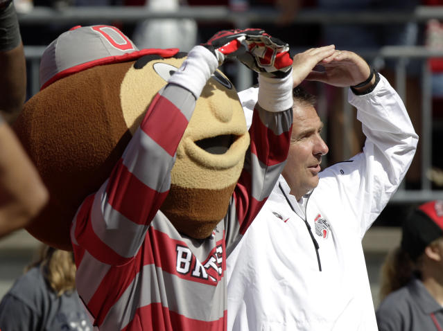 """Ohio State head coach Urban Meyer, right, sings """"Carmen Ohio"""" while standing next to school mascot Brutus Buckeye after their 76-0 win over Florida A&M in an NCAA college football game Saturday, Sept. 21, 2013, in Columbus, Ohio. (AP Photo/Jay LaPrete)"""