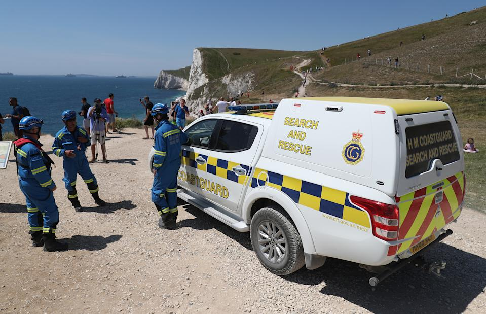 Members of HM Coastguard Search and Rescue at Durdle Door, near Lulworth, despite Dorset Council announcing that the beach was closed to the public after three people were seriously injured jumping off cliffs into the sea.