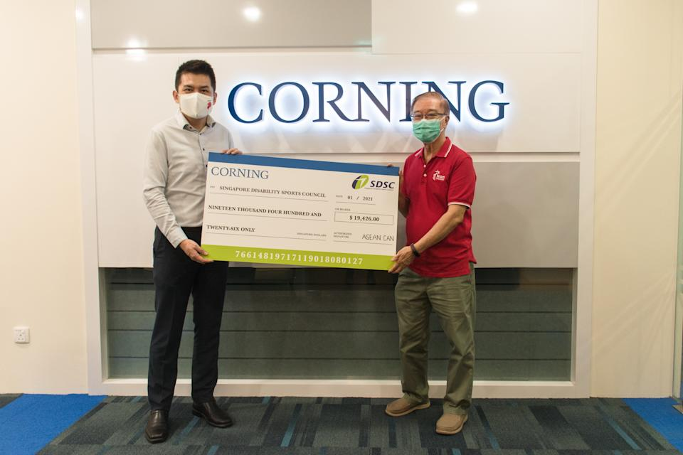 Corning International (ASEAN region) general manager Ho Cheong Tong (left) hands a cheque of $19,426 to Singapore Disability Sports Council honorary secretary Ho Cheng Kwee. (PHOTO: SDSC)