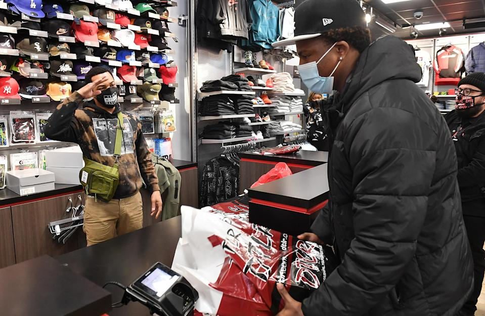 <p>T.I. gets into the giving spirit and gifts a student from Next Level Boys Academy clothes and shoes during the rapper's Harris Community Works Holiday Caravan at DTLR on Monday in Atlanta.</p>