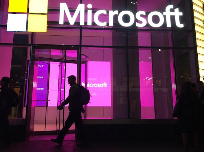 In this Nov. 10, 2016, photo, people walk near a Microsoft office in New York.
