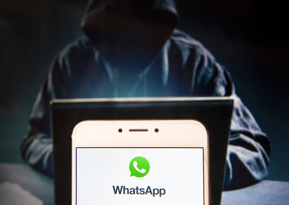 HONG KONG - 2018/11/22: Encrypted instant messaging application WhatsApp logo is seen on an Android mobile device with a figure of hacker in the background. (Photo by Miguel Candela/SOPA Images/LightRocket via Getty Images)