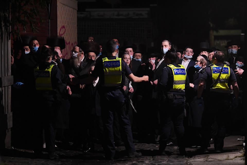 Victoria Police stand guard outside of building near a Ripponlea synagogue in Melbourne on Tuesday night after an illegal gathering. Source: Getty