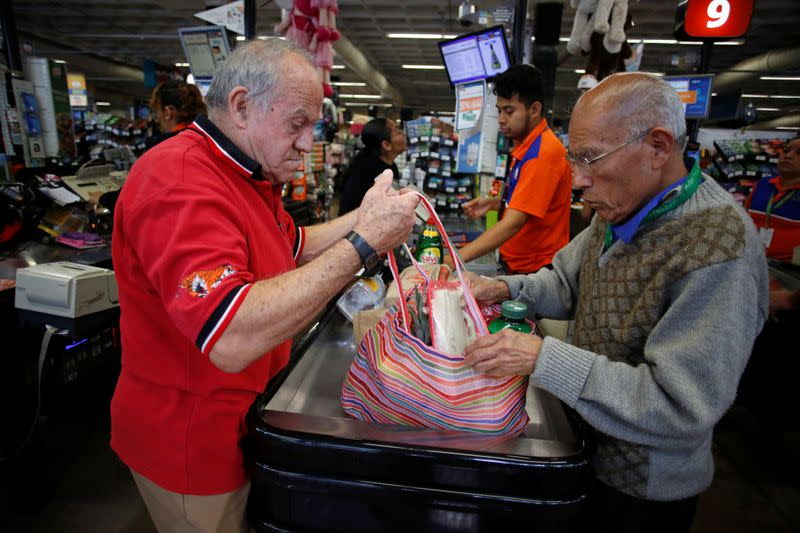 An employee helps a man to arrange groceries in a bag at a supermarket which no longer provides plastic bags for customers to carry products, in Mexico City