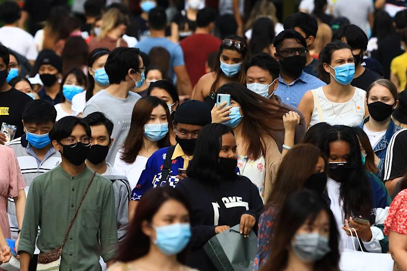 SINGAPORE - JUNE 20: People wearing protective masks walk along Orchard Road shopping belt on June 20, 2020 in Singapore. From June 19, Singapore started to further ease the coronavirus (COVID-19) restrictions by allowing social gatherings up to five people, re-opening of retail outlets and dining in at food and beverage outlets, subjected to safe distancing. Parks, beaches, sports amenities and public facilities in the housing estates will also reopen. However, large scale events, religious congregations, libraries, galleries and theatres will remain closed. (Photo by Suhaimi Abdullah/Getty Images)