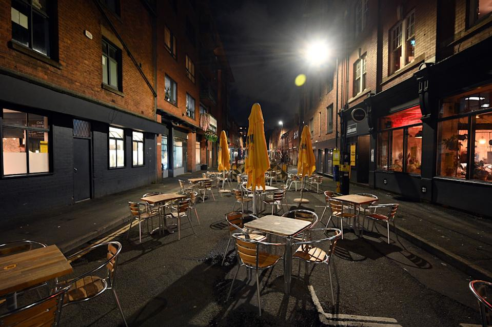 Empty tables and chairs at an outdoor eating area in Manchester