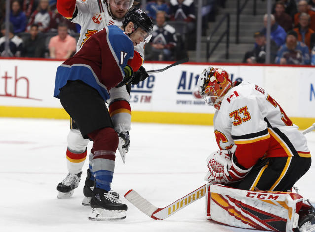 Colorado Avalanche left wing Matt Calvert, front left, reacts as his shot is stopped by Calgary Flames goaltender David Rittich, right, as defenseman Rasmus Andersson fights to keep Calvert out from in front of the net in the first period of an NHL hockey game Monday, Dec. 9, 2019, in Denver. (AP Photo/David Zalubowski)