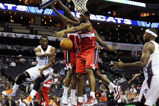 Charlotte Bobcats guard Kemba Walker (15) passes around Washington Wizards forward Kevin Seraphin (13) to Bobcats center Brendan Haywood (33) during the first half of an NBA preseason basketball game in Charlotte, N.C., Sunday, Oct. 7, 2012. (AP Photo/Mike McCarn)