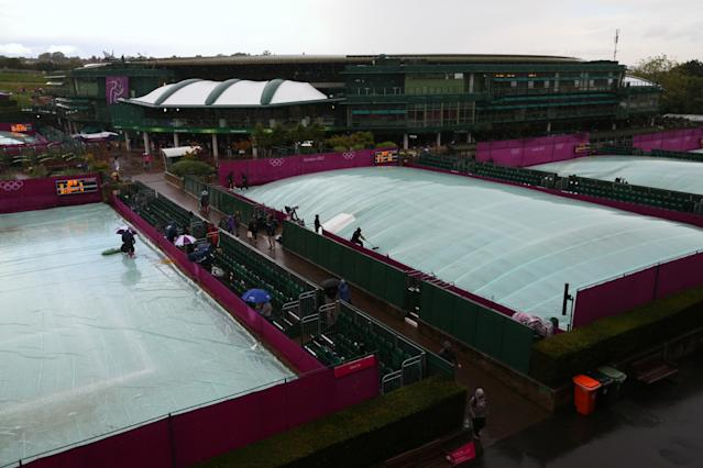 LONDON, ENGLAND - JULY 29: Rain covers protect the courts as rain delays play on Day 2 of the London 2012 Olympic Games at the All England Lawn Tennis and Croquet Club in Wimbledon on July 29, 2012 in London, England. (Photo by Clive Brunskill/Getty Images)