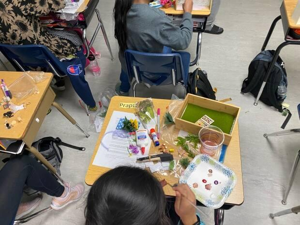 Prapti Ghelani, a student at Ethel Milliken School in Regina, constructs a memory box dedicated to a senior at a long-term care facility. (Carlie Brentnell - image credit)