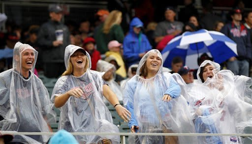 Minnesota Twins fans smile during a rain delay against the Detroit Tigers in the sixth inning of their baseball game in Minneapolis, Saturday, May 26, 2012. (AP Photo/Andy King)
