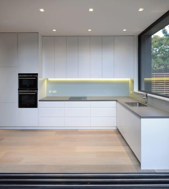 "<p>But what exactly is going in inside that new extension? A <a rel=""nofollow"" href=""https://www.homify.co.uk/rooms/kitchen"">kitchen</a>, it turns out! And just like the exterior façade, the interior spaces are quite high-style, elegant and super modern. </p><p>Notice the clean and serene style achieved by not only having the cabinetry adorned in a snow-white hue, but also not letting the cabinets and drawers have any knobs or pulls.</p>  Credits: homify / Ciarcelluti Mathers Architecture"