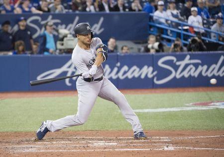 Mar 29, 2018; Toronto, Ontario, CAN; New York Yankees right fielder Giancarlo Stanton (27) hits a home run in the ninth inning during the Toronto Blue Jays home opener at Rogers Centre. The New York Yankees won 6-1. Mandatory Credit: Nick Turchiaro-USA TODAY Sports