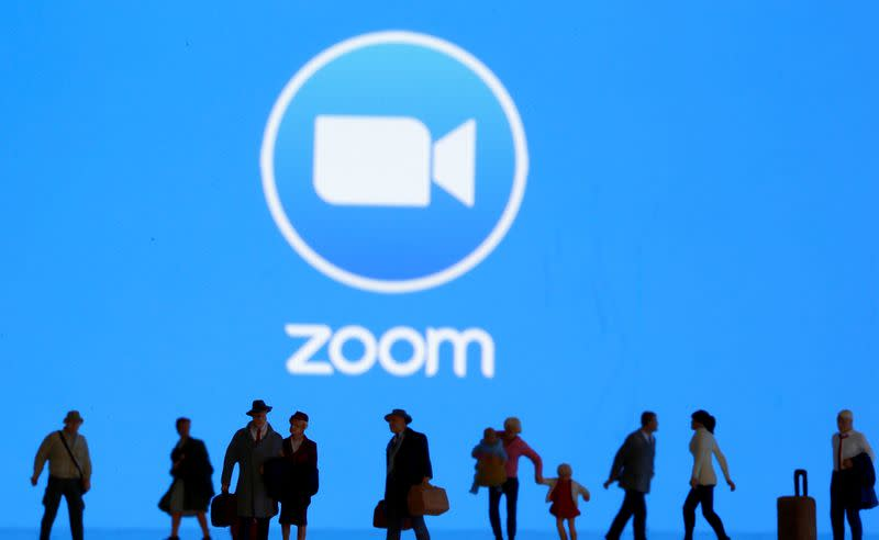 FILE PHOTO: Small toy figures are seen in front of diplayed Zoom logo