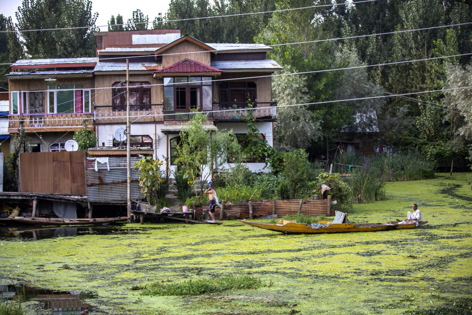 A Kashmiri man takes bath as boatman moves near him in the interior of Dal Lake in Srinagar, Indian controlled Kashmir, Saturday, Aug. 28, 2021. Weeds, silt and untreated sewage are increasingly choking the sprawling scenic lake, which dominates the city and draws tens of thousands of tourists each year. (AP Photo/Mukhtar Khan)