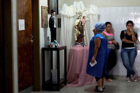 A woman prays in front of religious images at the pediatric ICU area at the Universitary Hospital in Merida, Venezuela June 17, 2016. REUTERS/Marco Bello